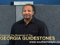 Image of host Darrell Lee standing in front of 3-D replica of Georgia Guidestones
